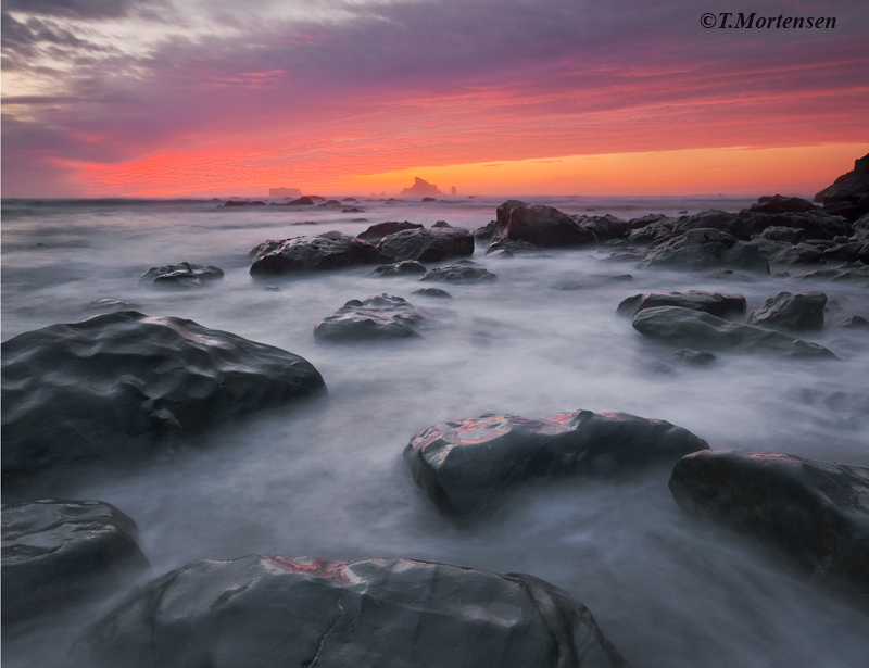 A long exposure provides a silky feel to the incoming tide while an amazing vibrant sunset illuminates the sky.
