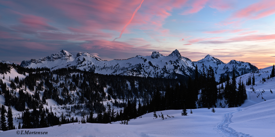Tatoosh Mountain Range under an incredible sunset sky filled with lenticular clouds and a funnel cloud while snowshoeing and...